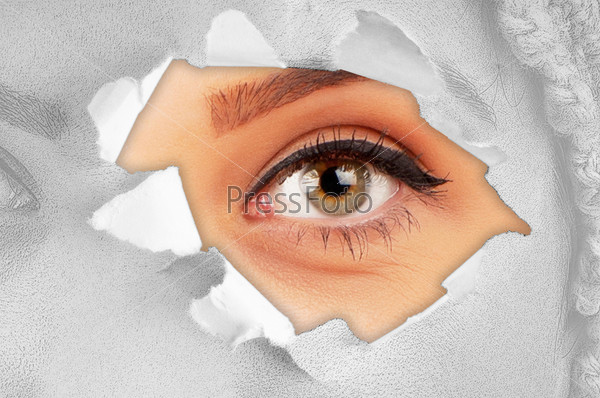 Woman eye through hole in paper