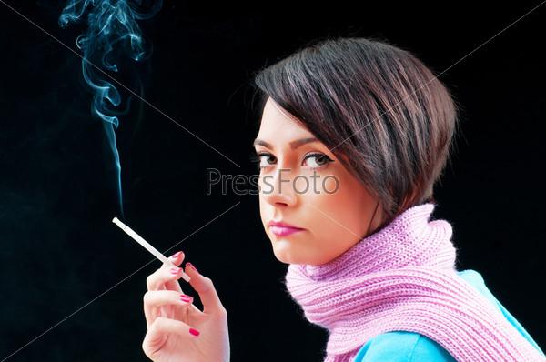 Young girl smoking on black