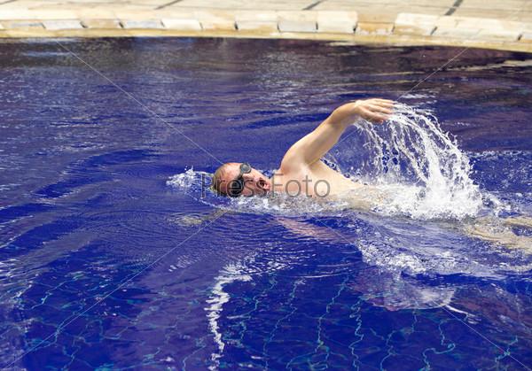 Молодой человек плавает в бассейне