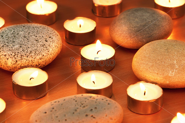 Burning candles and pebbles for aromatherapy session