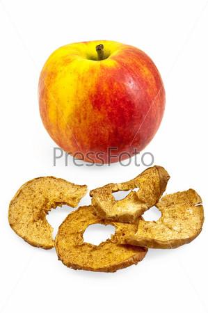 Красно-желтое яблоко и яблочные чипсы на белом фоне