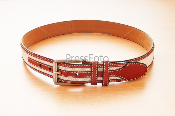 Leather belt on the wooden background