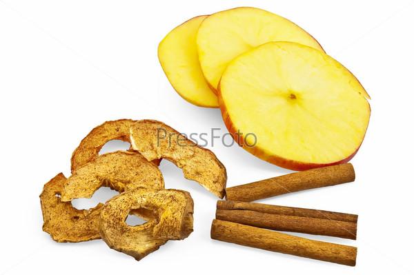 Ломтики яблока, палочки корицы и яблочные чипсы на белом фоне