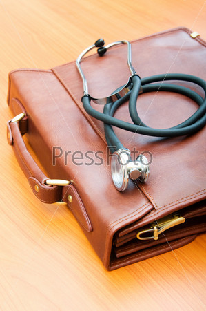 Doctor's case with stethoscope against wooden background