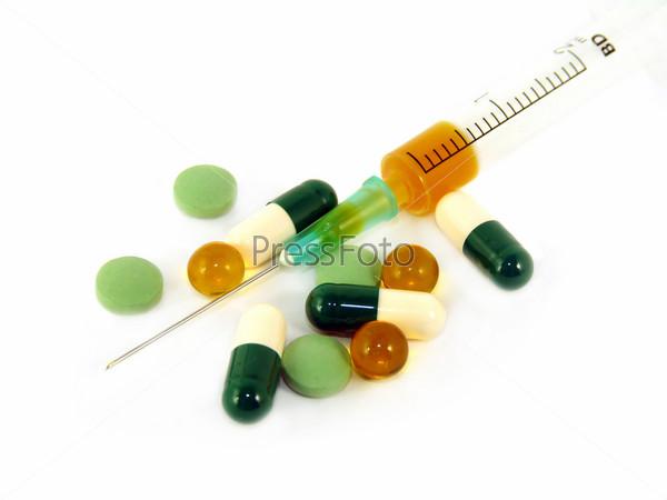 Syringe and pills isolated on white background