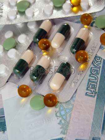 Tablets against the backdrop of the money. Treatment costs