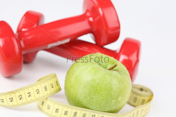 Гантели, яблоко и сантиметровая лента, изолированные на белом фоне