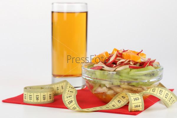 Сок, фруктовый салат и сантиметровая лента, изолированные на белом фоне