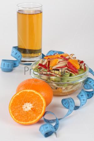 Сок, фруктовый салат и сантиметровая лента, изолированные на светлом фоне