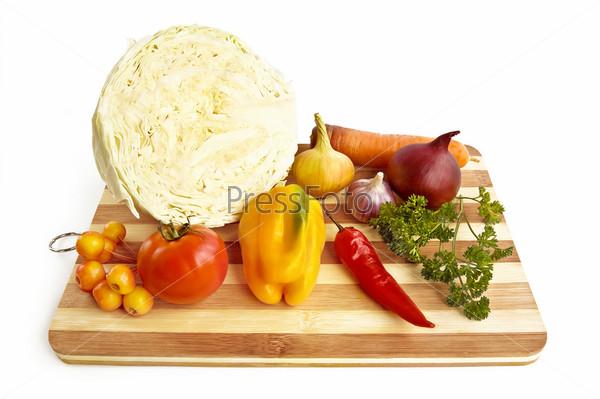 Разнообразные овощи на разделочной доске, изолированные на белом фоне