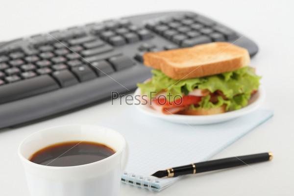 Сэндвич и чашка кофе на офисном столе