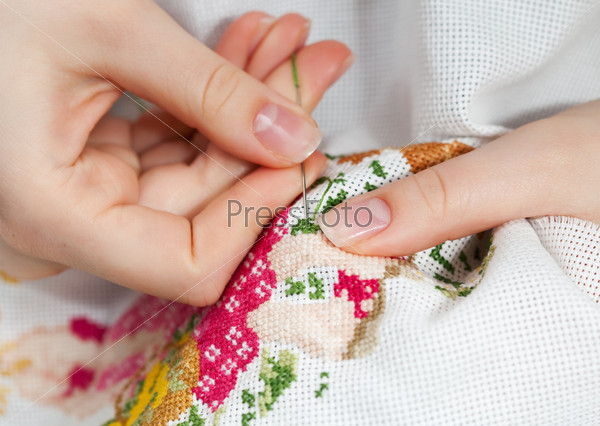 Женские руки за вышиванием