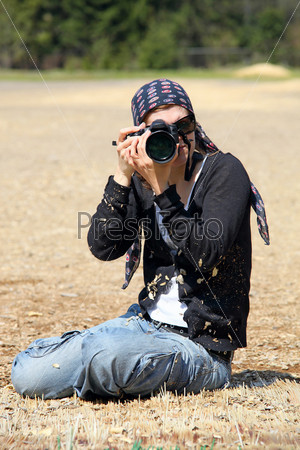 Женщина-фотограф сидит на земле