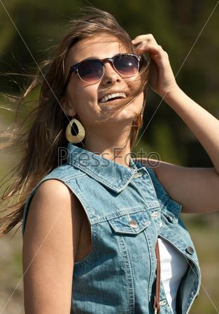 Фотография на тему Портрет улыбающейся девушки в солнечных очках и  джинсовом жилете 6fd5b7b4e31