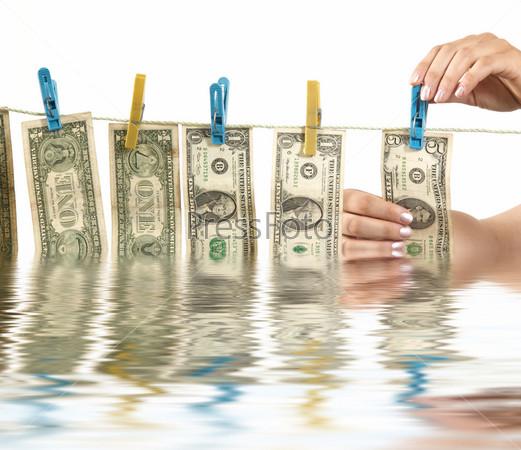 Фотография на тему Руки развешивают доллары на веревку для белья