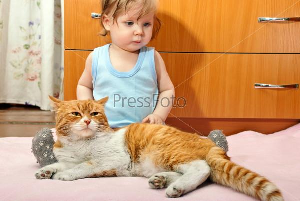 Маленький мальчик сидит с рыжей кошкой на розовом одеяле