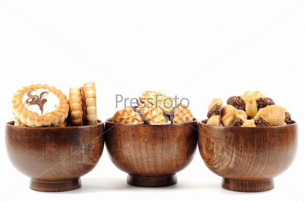 Разное печенье в деревянной тарелке на белом фоне