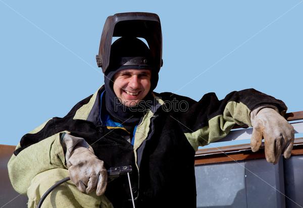 Сварщик в специальной маске на фоне голубого неба