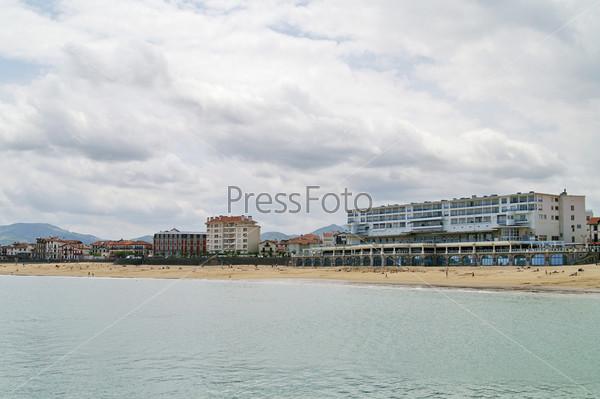 Здания и песчаный пляж на берегу океана