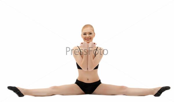 Фотография на тему Гимнастка в черном костюме сидит на шпагате, изолированная на белом фоне