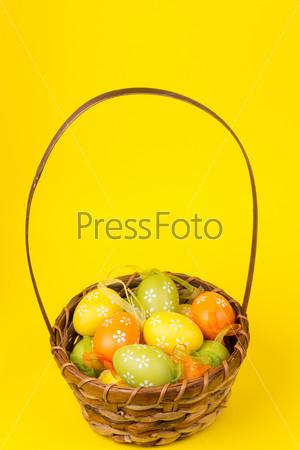 Фотография на тему Пасхальные яйца в корзине на желтом фоне