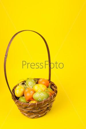 Пасхальные яйца в корзине на желтом фоне