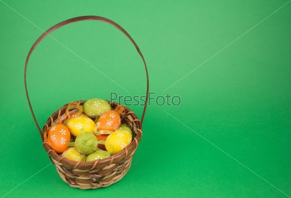 Фотография на тему Пасхальные яйца в корзине на зеленом фоне