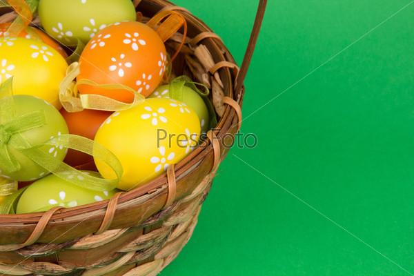 Пасхальные яйца в корзине на зеленом фоне