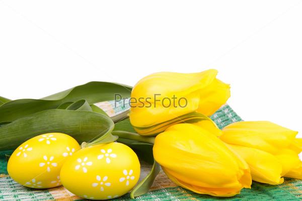 Пасхальные яйца и желтые тюльпаны на клетчатой скатерти