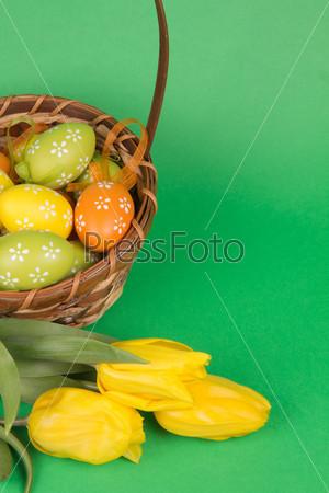 Пасхальные яйца в корзине и тюльпаны на зеленом фоне