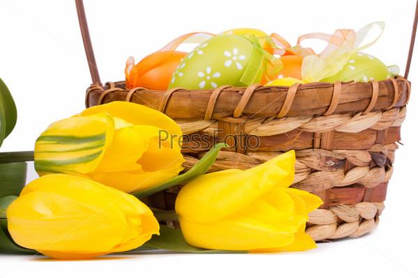 Фотография на тему Пасхальные яйца в корзине и тюльпаны на белом фоне