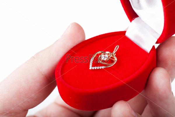 Красная подарочная коробка с ювелирным изделием в руке
