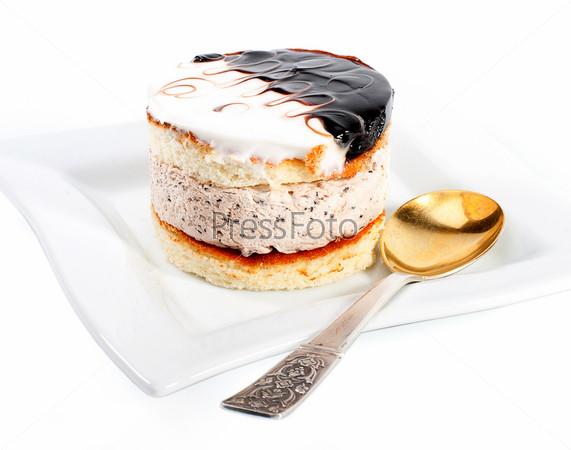 Кремовый торт на тарелке с ложкой на белом фоне