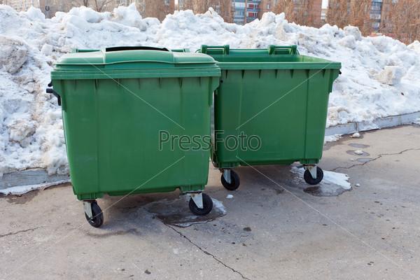 Два зеленых мусорных контейнеров в зимнем парке