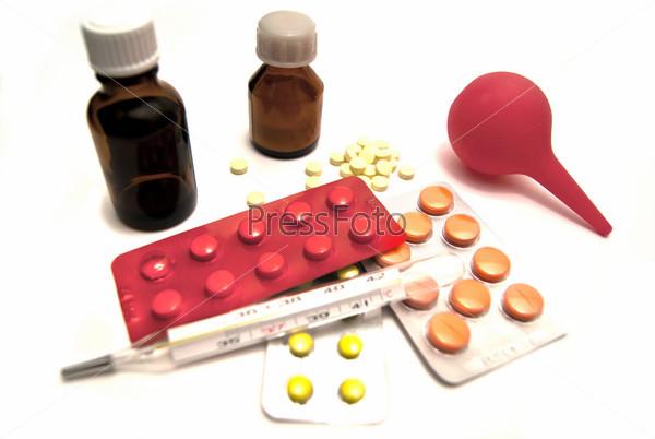 Таблетки, клизма и термометр на крупным планом на белом фоне
