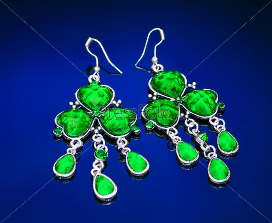 Серьги с зелеными камнями на синем фоне