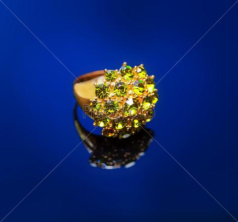 Фотография на тему Кольцо с зеленым изумрудом на синем фоне