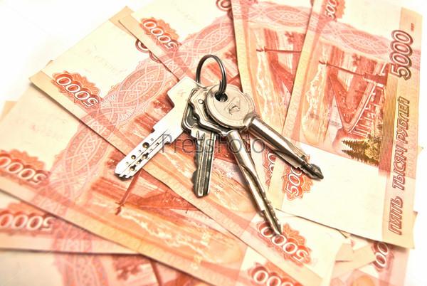 Банкноты и ключи на белом фоне