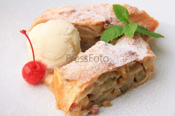 Фотография на тему Штрудель с яблоками, шарик ванильного мороженого, веточка мяты и вишня, посыпанные сахарной пудрой, на белом фоне