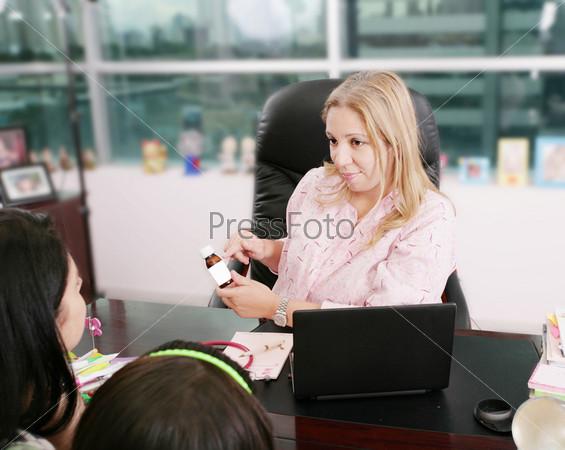 Доктор выписывает рецепт для молодой пациентки во время визита в кабинете