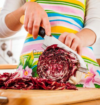 Фотография на тему Руки женщины разрезают красную капусту