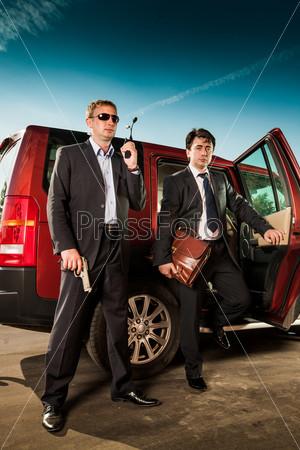 Телохранитель и его босс у автомобиля