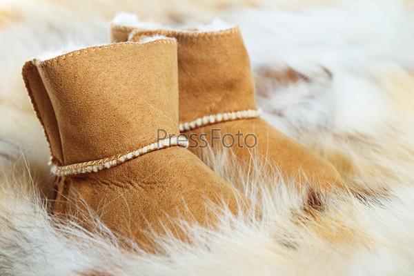 Фотография на тему Пара коричневых зимних сапог на фоне меха лисы