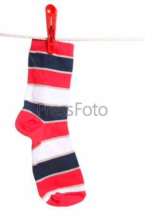 Полосатый носок висит на веревке для белья, изолированный на белом фоне