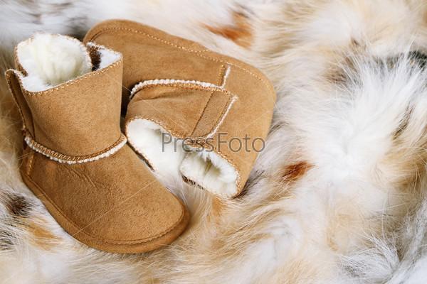 Пара коричневых зимних сапог на фоне меха лисы