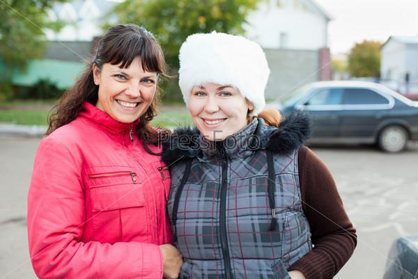 Две подруги стоят и улыбаются вместе на улице