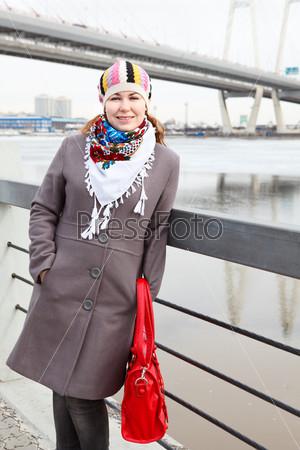 Фотография на тему Улыбающаяся женщина в шарфе стоит на набережной