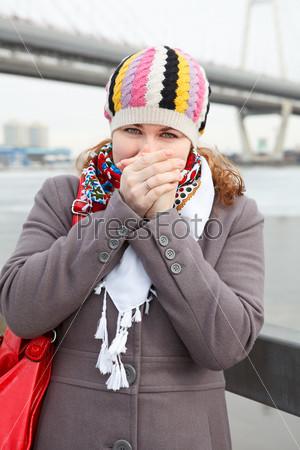 Замерзшая женщина в шарфе стоит на набережной
