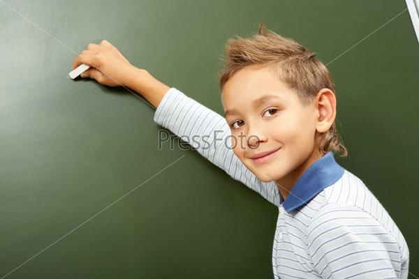 Мальчик пишет на доске
