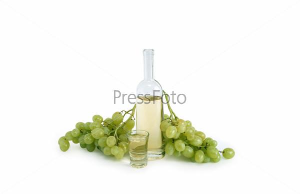 Фотография на тему Открытая бутылка итальянской водки граппа, рюмка и гроздья винограда на белом фоне